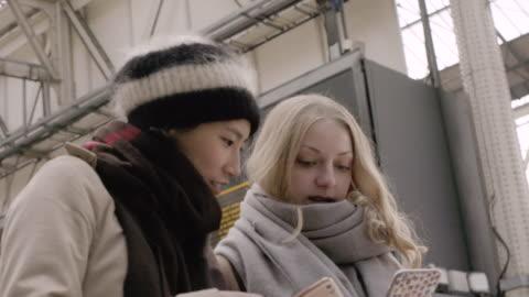 vidéos et rushes de women looking at phone and the departure board in train station. - montrer la voie