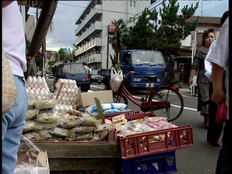stockvideo's en b-roll-footage met women looking at produce outside shop and entering shop - 1991