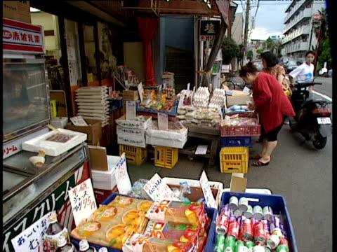 stockvideo's en b-roll-footage met women looking at produce outside shop - 1991