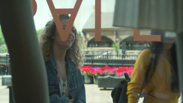 vídeos de stock e filmes b-roll de women looking through store window - loja de roupa