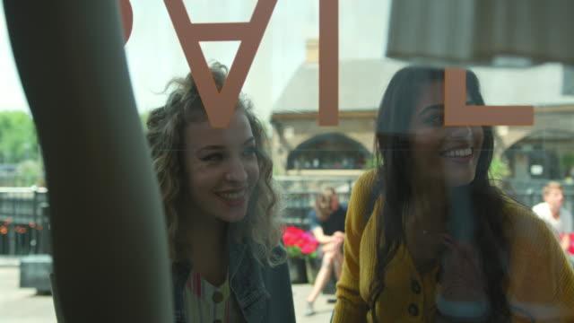 women looking through store window - 指差す点の映像素材/bロール