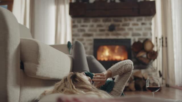 vidéos et rushes de femmes se couchant et parlant au téléphone - foyer de cheminée