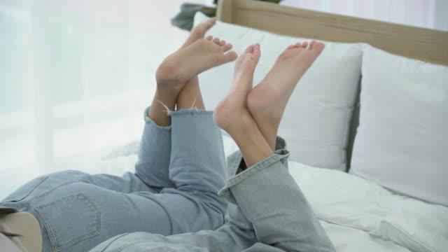 vídeos y material grabado en eventos de stock de mujeres acostadas en la cama con las piernas cruzadas - descalzo