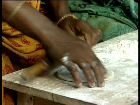 vídeos de stock, filmes e b-roll de women make chapatis at an emergency bakery set up after flooding - rolo de pastel