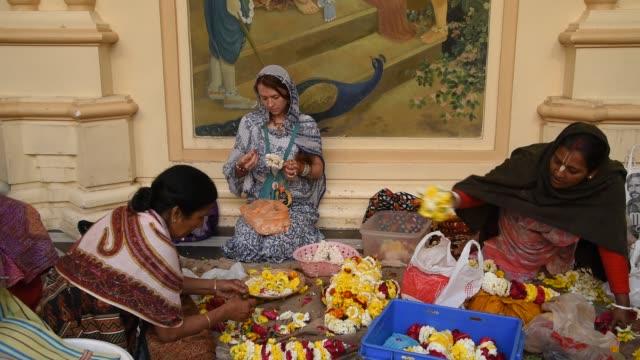vídeos y material grabado en eventos de stock de women making garland at iskcon temple at vrindavan, india. - vrindavan