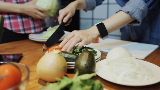 vídeos de stock e filmes b-roll de women making salad - domestic kitchen
