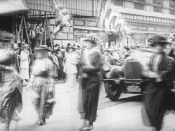 women marching + car on street at suffragette victory parade / boston / newsreel - frauenrechte stock-videos und b-roll-filmmaterial