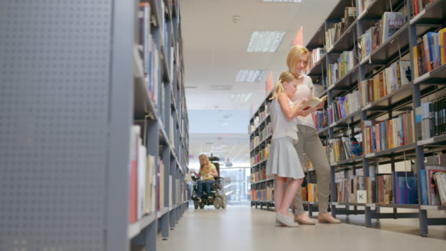 ds women, men and children spending time in the library - library stock videos & royalty-free footage