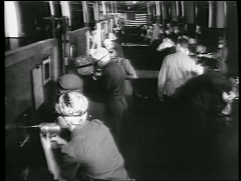stockvideo's en b-roll-footage met b/w 1944 women men with goggles riveting in rows at defense plant / world war ii / industrial - first line of defense filmtitel