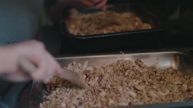 women mixing baked granola - baking sheet stock videos & royalty-free footage