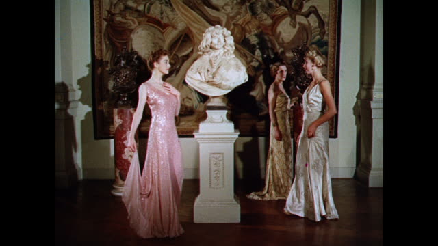 ws women model long evening gowns in front of a large tapestry / uk - evening gown stock videos and b-roll footage