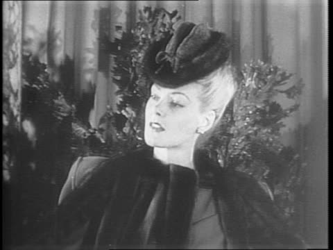 vidéos et rushes de women model various fur fashions including coats hats and stoles / first model shows off a reversible mink coat with red wool lining / next model... - châle