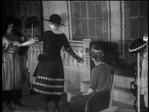 B/W 1917 women modeling dress for women sitting