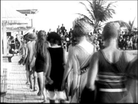 vídeos y material grabado en eventos de stock de view women modeling swimsuits on boardwalk at miami beach / newsreel - traje de baño de una pieza