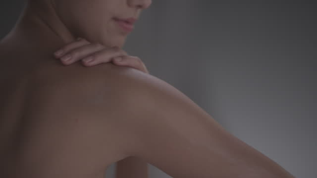 women moisturising shoulder and arm with cream - halbbekleidet stock-videos und b-roll-filmmaterial