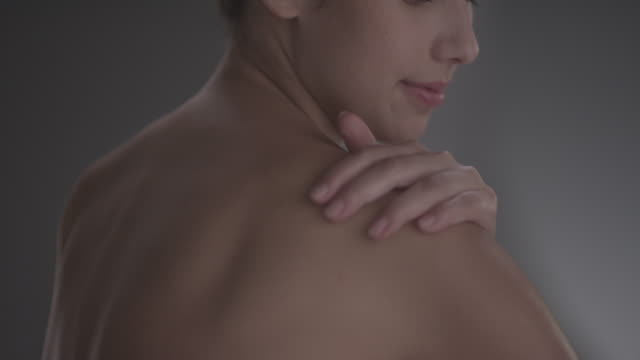 Women moisturising shoulder with cream