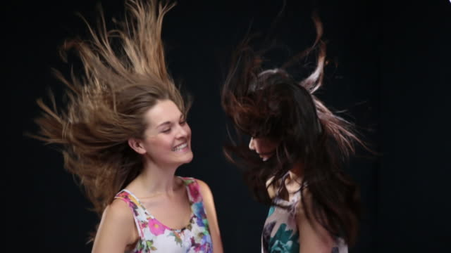 ms slo mo women moving heads from side to side, dancing and laughing, wind blowing hair around / london, greater london, united kingdom - greater london video stock e b–roll