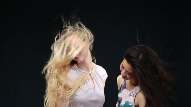 ms slo mo women moving heads side to side,laughing and hair moving in wind / london, greater london, united kingdom - greater london video stock e b–roll