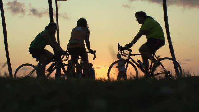 ws women on bikes against setting sun on waikiki beach / honolulu, hawaii, usa - dicke frauen am strand stock-videos und b-roll-filmmaterial