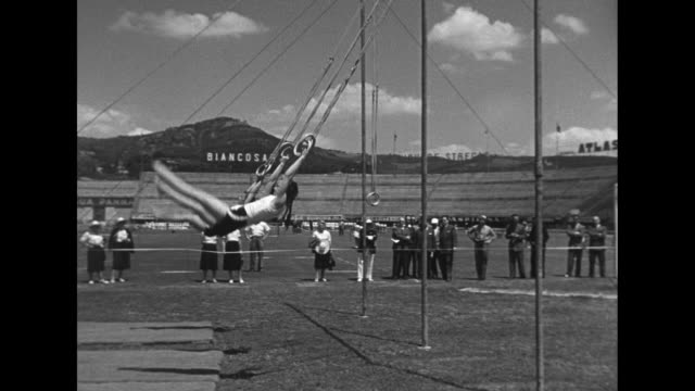 women on field holding flags, flag in front may be yugoslavian with french flag next to it; behind them first, second and third place winning... - akrobat bildbanksvideor och videomaterial från bakom kulisserna