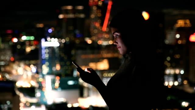 シティー ビューと携帯電話上の女性
