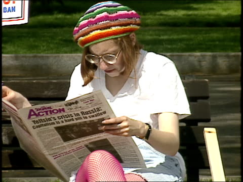 women on park bench with lesbian rights signs and reading newspaper - anno 1993 video stock e b–roll