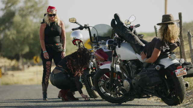 vidéos et rushes de women on road celebrating fixing broken down motorcycle / payson, utah, united states - payson