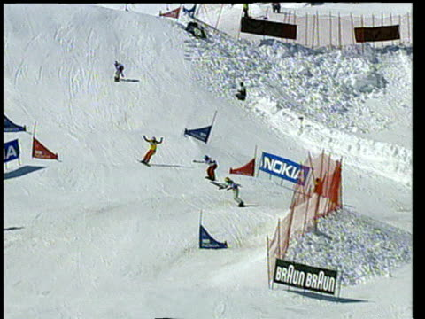 women on snowboards jump over ski jumps during race then congratulate each other at finish switzerland - huvudbonad bildbanksvideor och videomaterial från bakom kulisserna