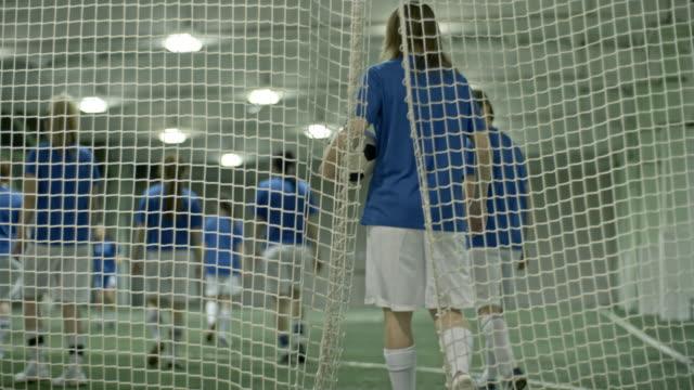 Women only soccer team entering indoor field for practice