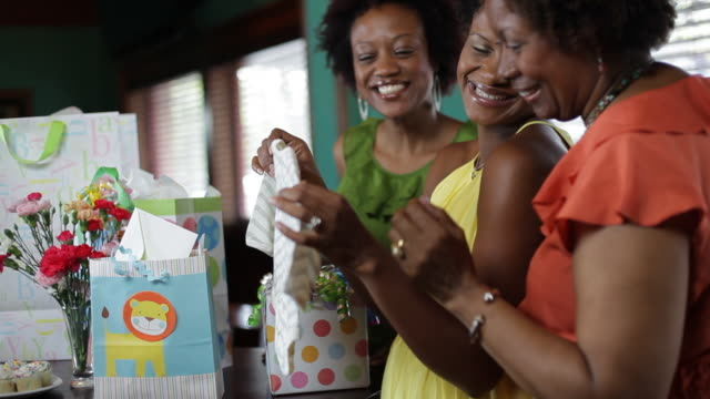 women open gifts at a baby shower. - baby shower video stock e b–roll
