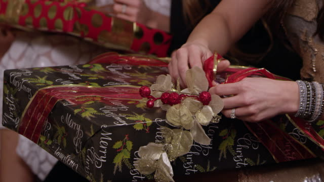 Women opening gifts at a Holiday Christmas party