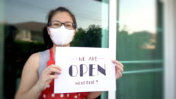 Women Owner holds Open sign at front restaurant