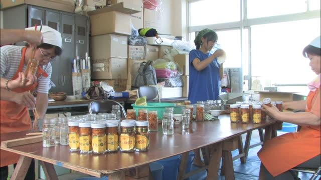 women package sea urchins in glass jars. - 缶詰にする点の映像素材/bロール