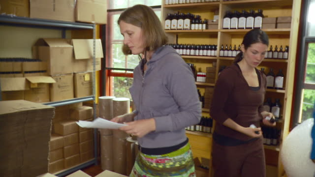 ms td women packing bottles into boxes in shop / burlington, vermont, usa. - 荷造り点の映像素材/bロール