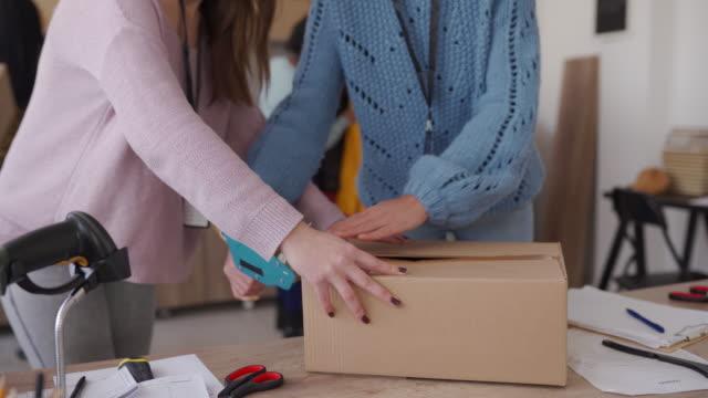 kvinnor packning kunder order i kartong för drop frakt - skicka aktivitet bildbanksvideor och videomaterial från bakom kulisserna