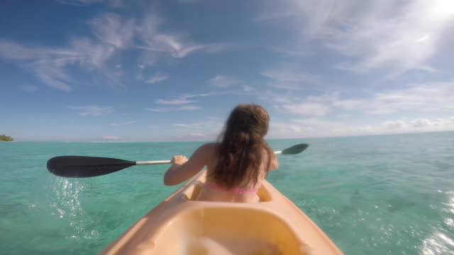 vídeos de stock, filmes e b-roll de women paddling kayak - huahine island