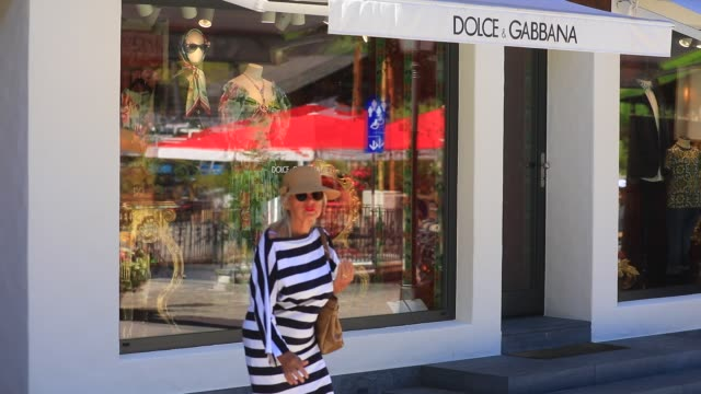 women passes next to italian luxury fashion house dolce & gabbana storefront on the promenade, a pedestrian street with luxury, food and artisan... - dolce & gabbana stock videos & royalty-free footage