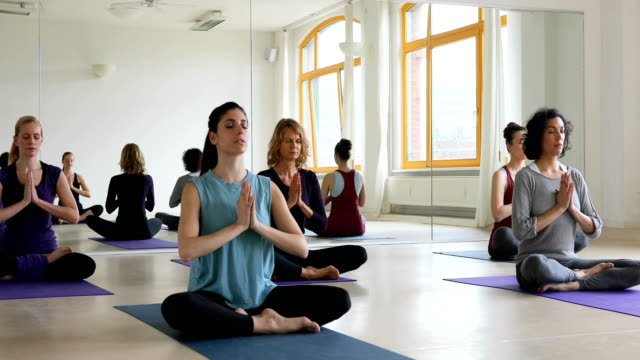 Women performing relaxation exercise in yoga class