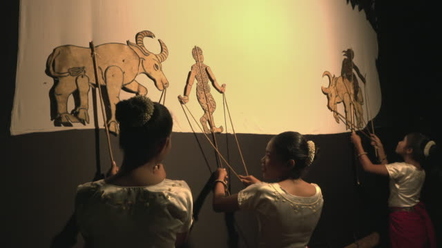 vídeos de stock e filmes b-roll de women performing traditional shadow puppet play - marionete