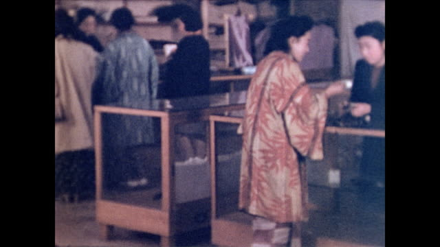 / women peruse the few pieces of merchandize in a depleted store / inspect brushes and fabric. nagasaki store in post war japan on january 24, 1946... - 百貨店点の映像素材/bロール