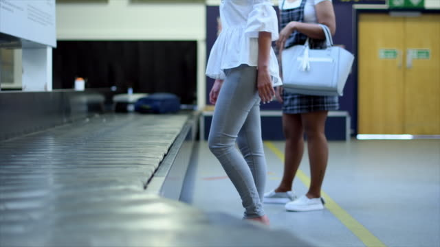women picking up luggage - wheeled luggage stock videos & royalty-free footage
