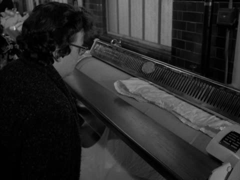women place their clean sheets through pressing rollers at a launderette. - waschsalon stock-videos und b-roll-filmmaterial