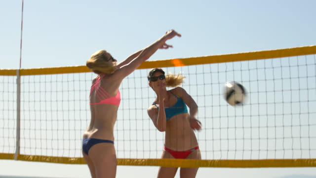 women players play beach volleyball and a player blocks the ball. - slow motion - volleyball sport stock videos & royalty-free footage