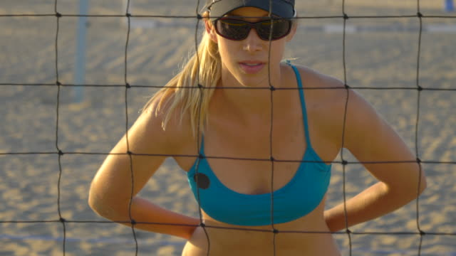 women players play beach volleyball and a player blocks the ball. - slow motion - 腰に手を当てる点の映像素材/bロール