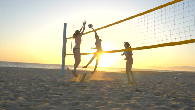 Women players play beach volleyball and a player blocks the ball.