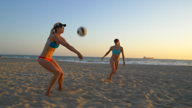 women players play beach volleyball and a player blocks the ball. - volleyball sport stock videos & royalty-free footage