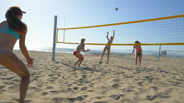 women players play beach volleyball and a player digs the ball. - slow motion - sonnenschild stock-videos und b-roll-filmmaterial