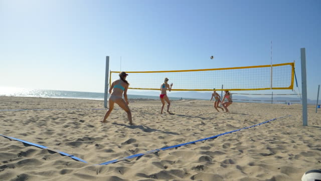women players play beach volleyball and a player digs the ball. - slow motion - filmed at 180 fps - sonnenschild stock-videos und b-roll-filmmaterial