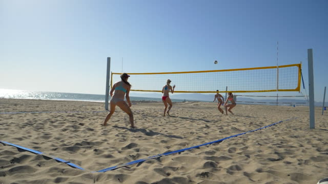 Women players play beach volleyball and a player digs the ball.
