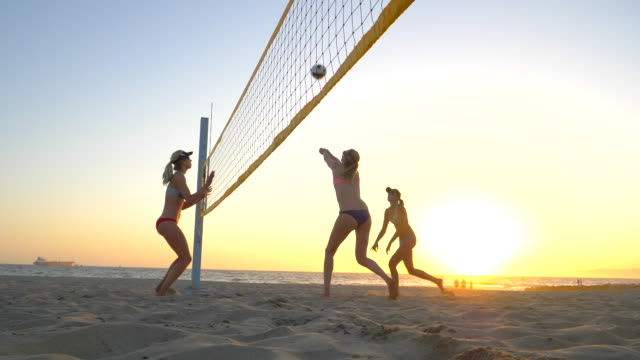 Women players play beach volleyball and a player hitting spiking the ball.